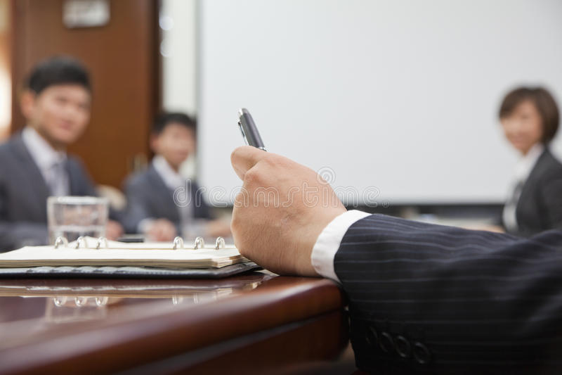 Fermez-vous de la main de l'homme d'affaires tenant un stylo photographie stock