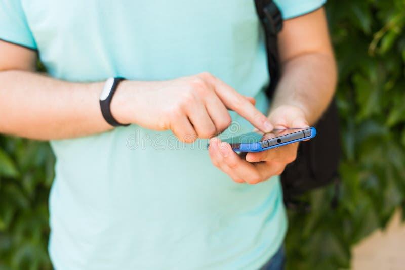 Fermez-vous de la main du ` s des hommes avec un traqueur de forme physique et un téléphone intelligent dehors photo stock