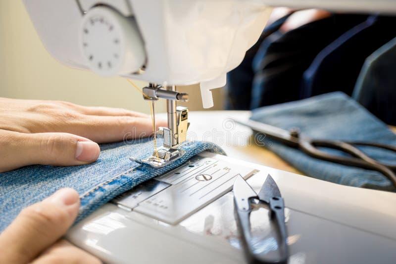 Fermez-vous de la main du ` s de tailleur fonctionnant avec la machine à coudre image libre de droits