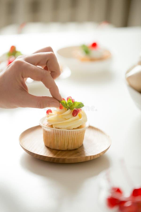 Fermez-vous de la main femelle décorant un petit gâteau avec la feuille en bon état image stock