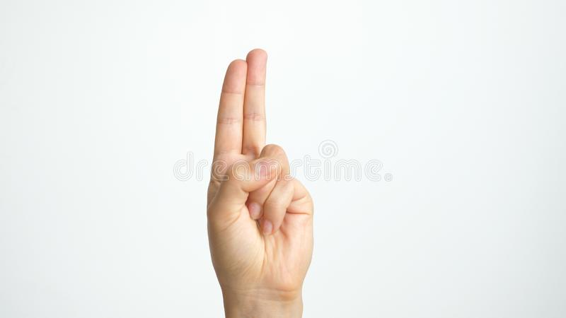 Fermez-vous de la main femelle d'isolement montre deux doigts d'isolement sur le fond blanc photographie stock