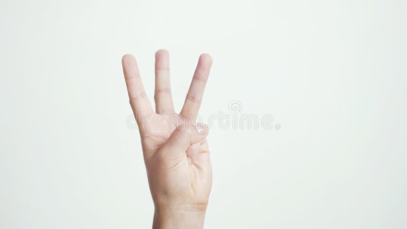 Fermez-vous de la main femelle d'isolement montre trois doigts d'isolement sur le fond blanc image stock