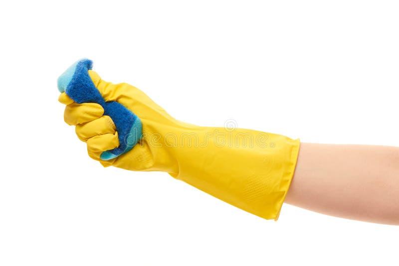Fermez-vous de la main femelle dans le gant en caoutchouc protecteur jaune serrant l'éponge bleue de nettoyage images stock