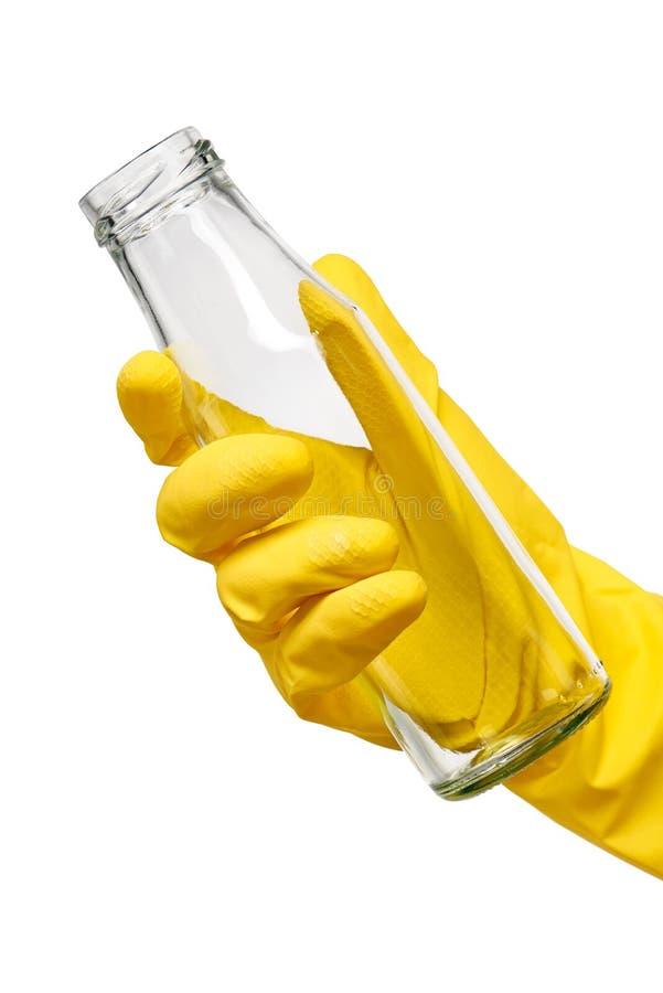 Fermez-vous de la main femelle dans le gant en caoutchouc protecteur jaune tenant la bouteille à lait en verre transparente propr photos libres de droits