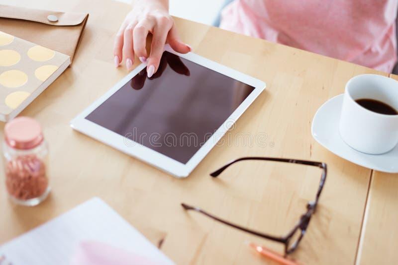 Fermez-vous de la main femelle sur le comprimé numérique images stock