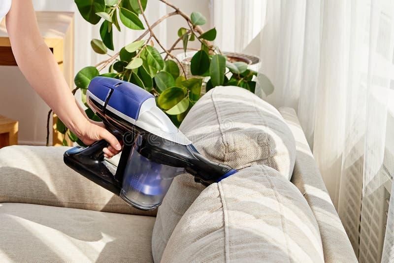 Fermez-vous de la main de femme avec l'aspirateur, l'espace de copie Sofa de nettoyage de femme avec l'aspirateur Ménage et resso photographie stock
