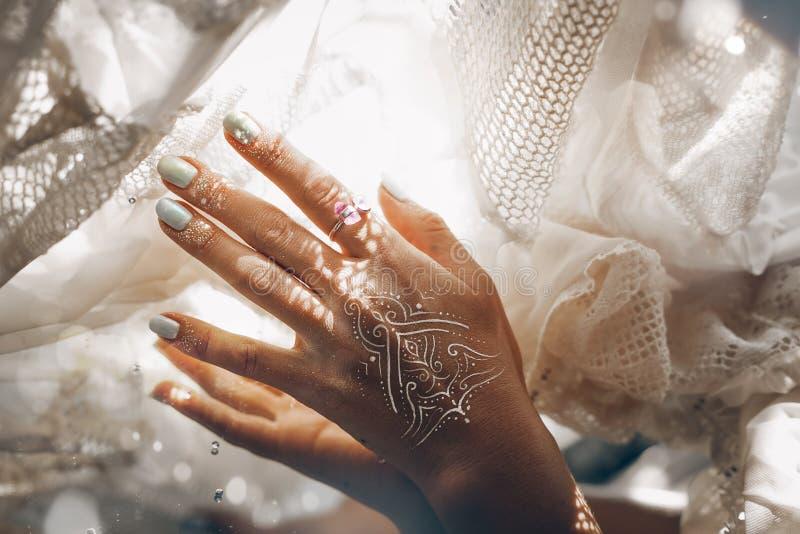 Fermez-vous de la main de femme avec le fabri bribal blanc émouvant de manucure photographie stock