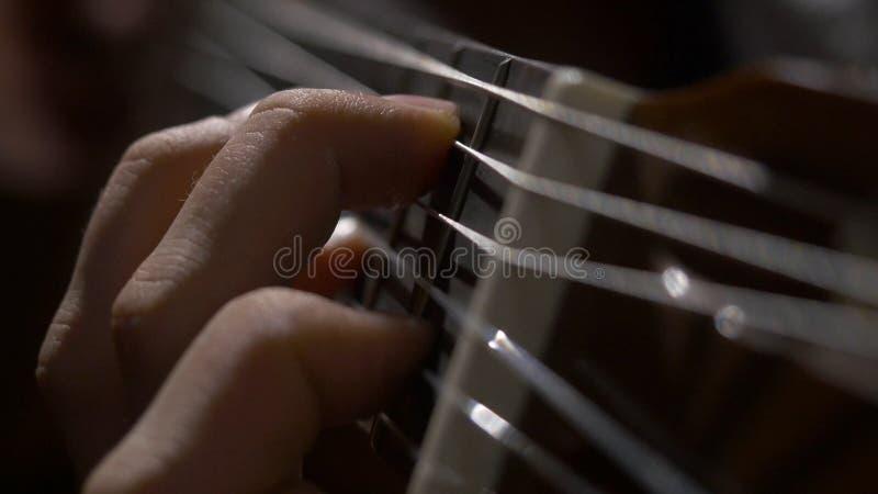 Fermez-vous de la main de guitariste jouant la guitare acoustique Fermez-vous vers le haut du tir d'un homme avec ses doigts sur  images stock