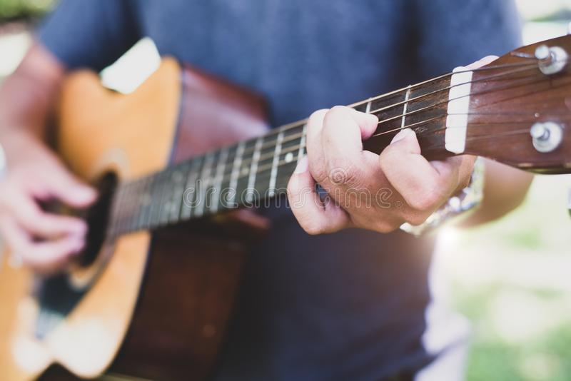 Fermez-vous de la main de guitariste jouant la guitare Concept de musical et d'instrument Th?me d'ext?rieur et de loisirs Foyer s photo libre de droits