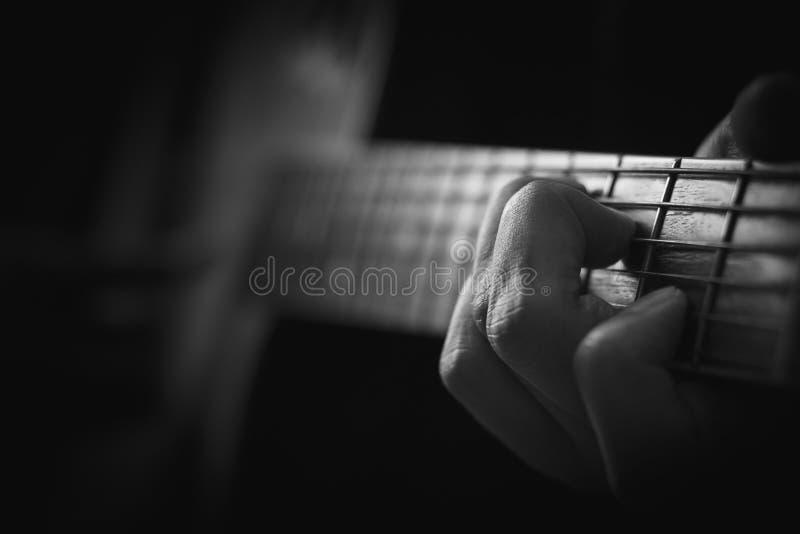 Fermez-vous de la main jouant la guitare acoustique à l'arrière-plan de mémoire photographie stock