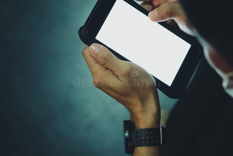 Fermez-vous de la main de l'homme à l'aide des téléphones intelligents mobiles dans l'obscurité photo libre de droits