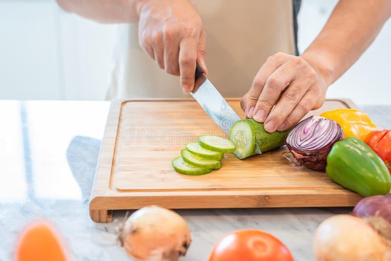 Fermez-vous de la main de l'homme faisant cuire et d?coupant le l?gume en tranches dans la cuisine pour pr?parer le d?ner avec so photos stock