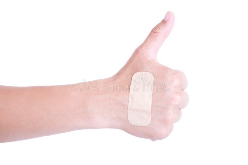 Fermez-vous de la main masculine avec les pouces o d'isolement d'emplâtre adhésif images stock
