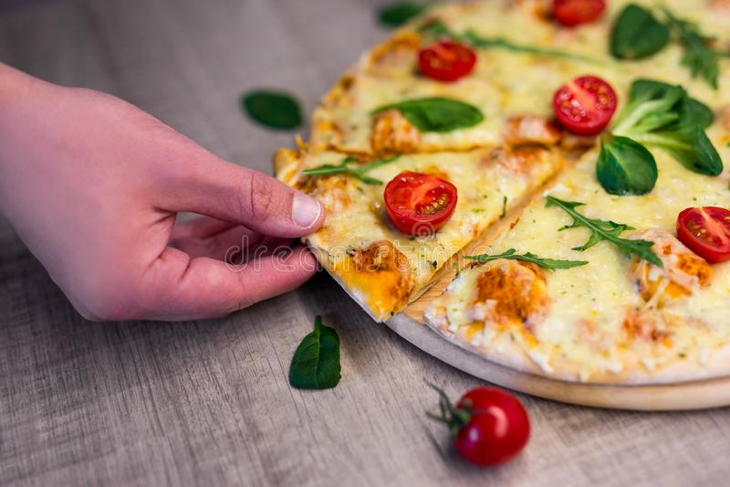 Fermez-vous de la main masculine prenant la tranche de pizza savoureuse avec des tomates et des herbes au-dessus de table en bois images stock