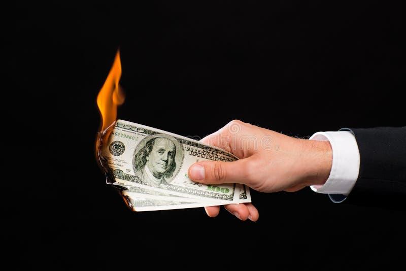 Fermez-vous de la main masculine tenant l'argent brûlant du dollar photographie stock libre de droits