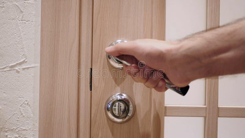 Fermez-vous de la main ouvrant la porte de la maison images stock