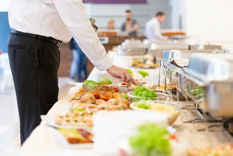 Fermez-vous de la main de serveur préparant en mettant la cuillère en salade sur la table de buffet photo stock