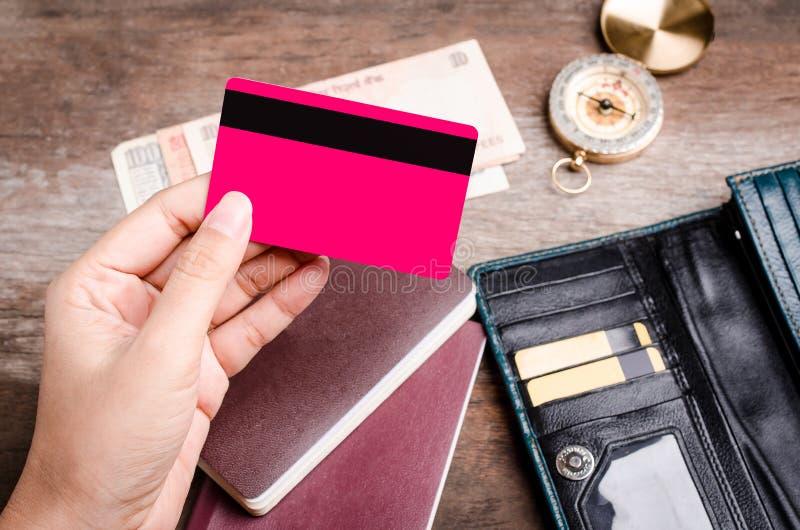 Fermez-vous de la main tenant la carte de crédit sur le fond en bois photos stock