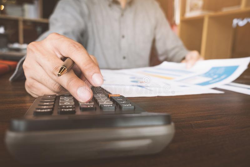 Fermez-vous de la main utilisant la calculatrice, homme d'affaires travaillant au bureau o image stock