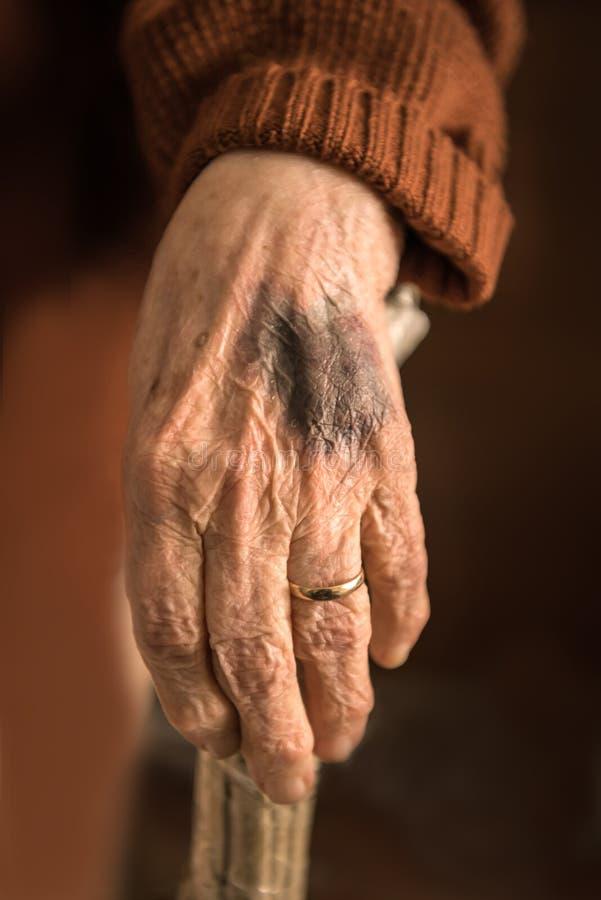 Fermez-vous de la main de la vieille femme froissée image stock