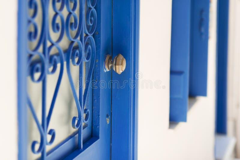 Fermez-vous de la maison typique d'architecture grecque avec la porte bleue, les fenêtres bleues et les cadres bleus images stock