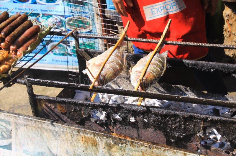 Fermez-vous de la nourriture traditionnelle de rue de barbecue avec deux poissons sur des brochettes sur le gril de charbon de bo photo stock