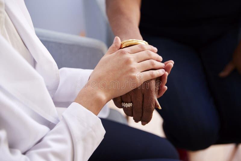 Fermez-vous de la patiente supérieure féminine de femme de docteur In Office Reassuring et de tenir ses mains photographie stock libre de droits