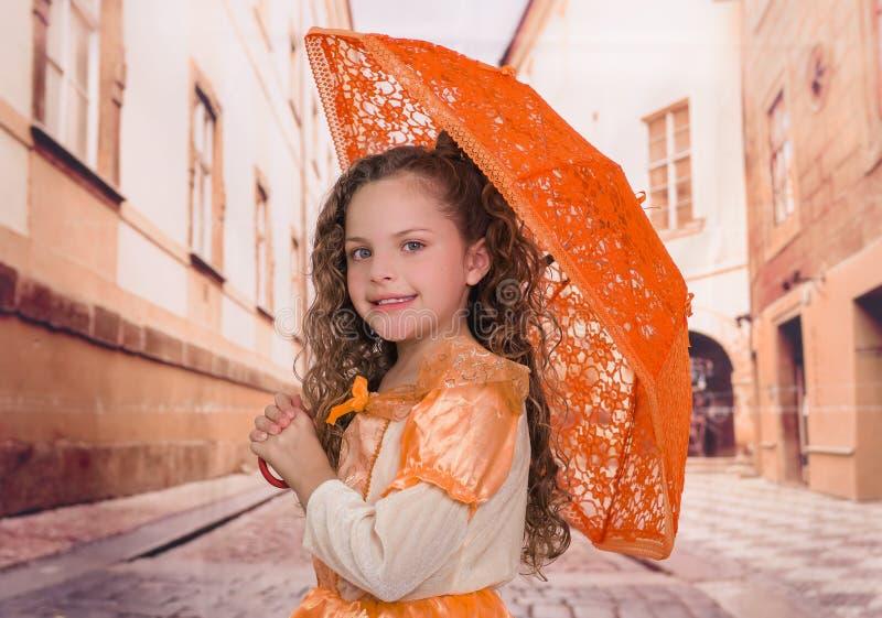 Fermez-vous de la petite belle fille bouclée utilisant un beau costume colonial et jugeant un parapluie orange dans brouillé image libre de droits