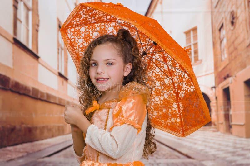 Fermez-vous de la petite belle fille utilisant un beau costume colonial et jugeant un parapluie orange dans brouillé image libre de droits