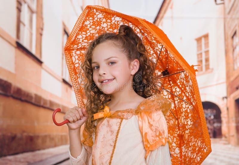 Fermez-vous de la petite belle fille utilisant un beau costume colonial et jugeant un parapluie orange dans brouillé image stock