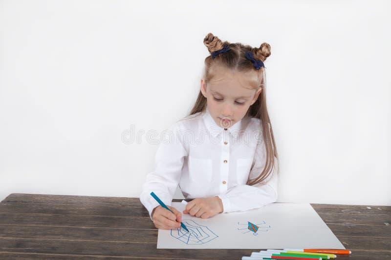Fermez-vous de la petite fille dans le chemisier blanc qui est concentré sur le dessin L'élève du cours préparatoire apprend comm photo libre de droits