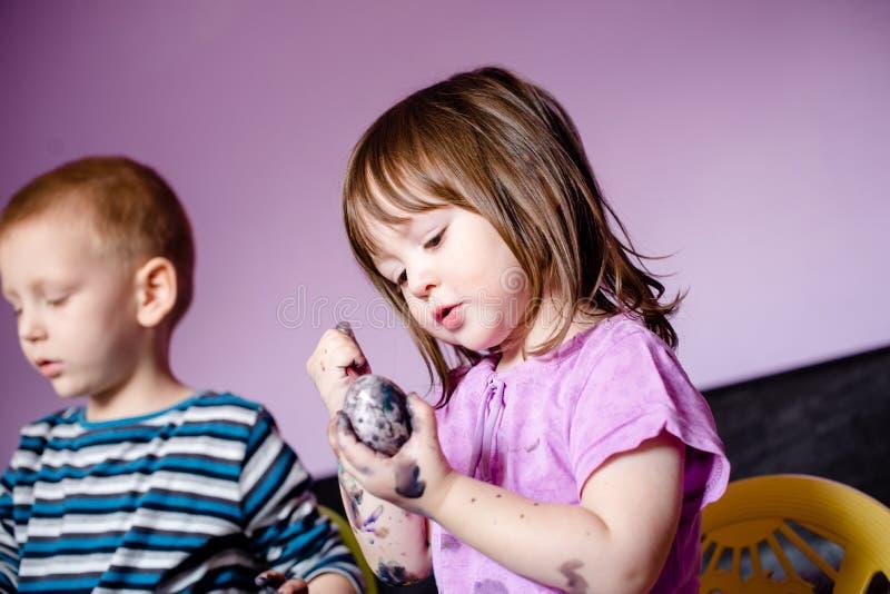 Fermez-vous de la petite fille mignonne employant des couleurs d'eau images stock