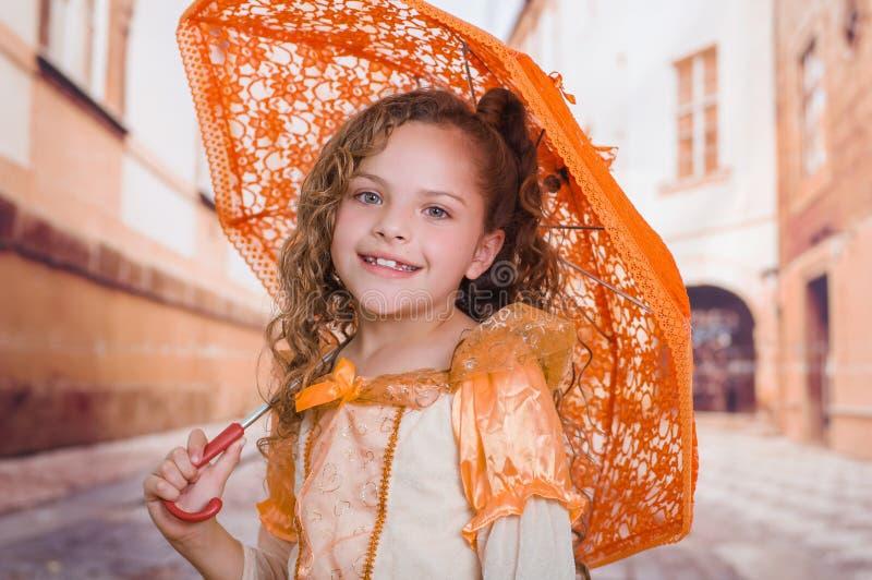 Fermez-vous de la petite fille utilisant un beau costume colonial et tenant un parapluie orange à un arrière-plan brouillé image stock