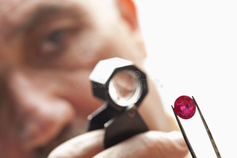 Fermez-vous de la pierre gemme avec le bijoutier regardant par la loupe photographie stock libre de droits