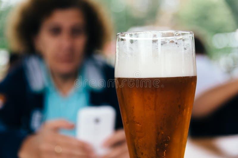 Fermez-vous de la pinte régénératrice de bière blonde contre la famille dans la barre photographie stock