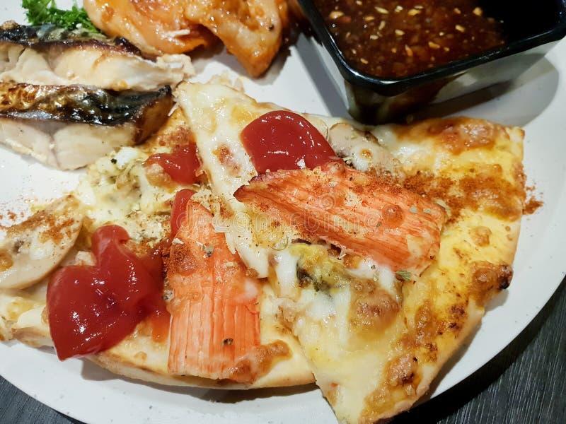 Fermez-vous de la pizza et de la sauce de fruits de mer du plat blanc images stock
