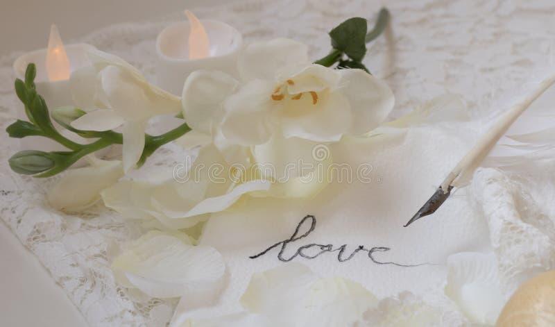 Fermez-vous de la plume d'oie qui écrit l'amour sur une serviette blanche, avec des fleurs et des bougies photographie stock