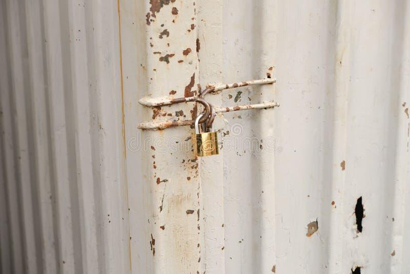 Fermez-vous de la porte en acier rouillée solidement verrouillée avec une protection d'or photo stock