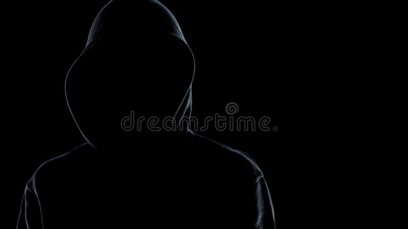 Fermez-vous de la position masculine sans visage de silhouette sur le fond noir, criminel photographie stock