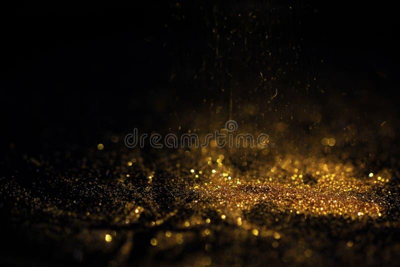 Fermez-vous de la poudre d'or avec des lumières de scintillement sur le fond noir photos stock