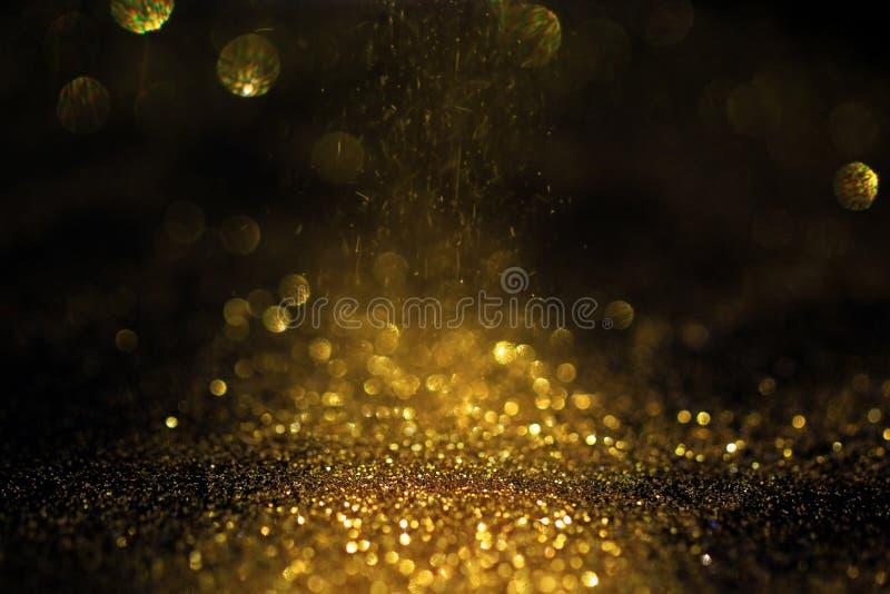 Fermez-vous de la poudre d'or avec des lumi?res de scintillement sur le fond noir image stock