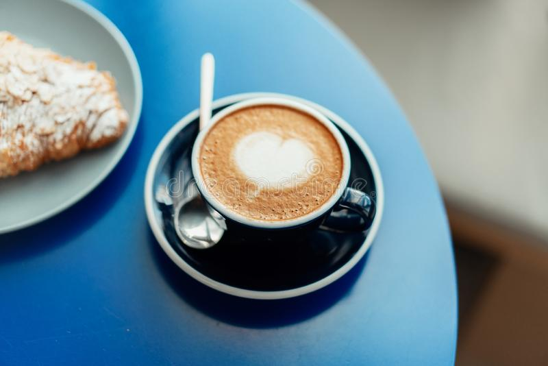 Fermez-vous de la tasse de café bleue sur la table en bois en café Concept de petit déjeuner savoureux images libres de droits