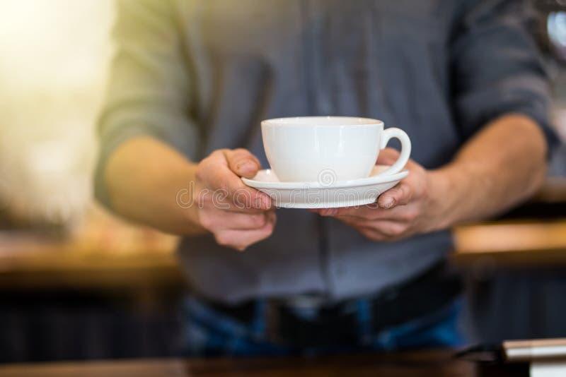 Fermez-vous de la tasse masculine de portion de barman de café frais Tasse de café dans les mains du serveur photos stock