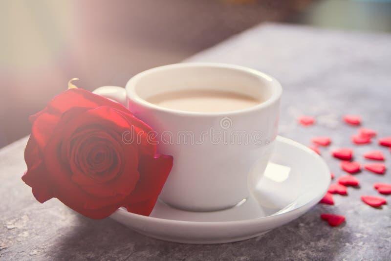 Fermez-vous de la tasse de thé avec la rose rouge et de petits coeurs de sucrerie sur la table photos stock