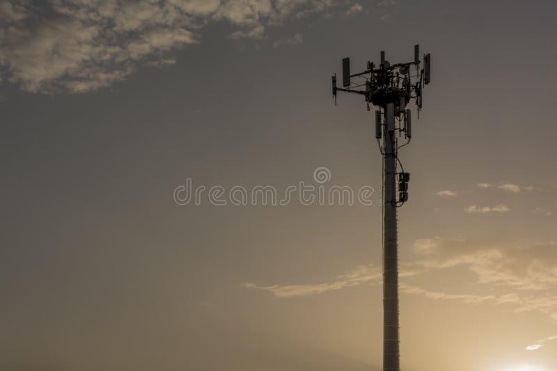Fermez-vous de la tour de téléphone portable au coucher du soleil photos stock