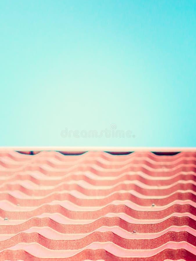 Fermez-vous de la tuile rose de texture de toit avec le ciel bleu photos libres de droits