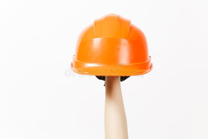 Fermez-vous de la verticale femelle de main juge le casque orange de construction protectrice d'isolement sur le fond blanc instr images libres de droits