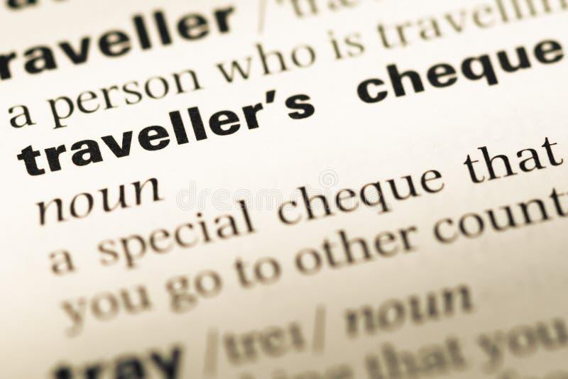 Fermez-vous de la vieille page anglaise de dictionnaire avec le chèque de voyage de mot photographie stock