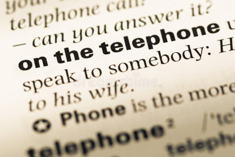 Fermez-vous de la vieille page anglaise de dictionnaire avec le mot au téléphone photographie stock