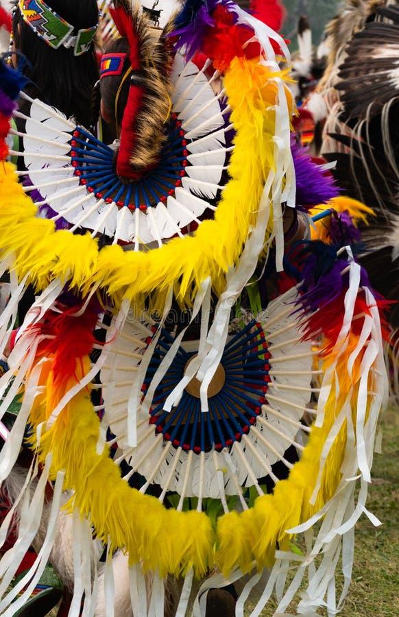 Fermez-vous de mouvement et de coiffe de plume jaune et blanche sur un danseur de fantaisie images stock